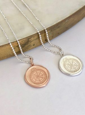 coin necklace with a compass stamped onto it in rose gold or silver