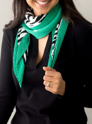 model wearing a pleated scarf with animal print and a green border