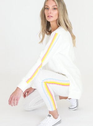 White sweater with yellow, blue and orange stripes down the sleeve